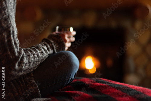 Photo sitting in cozy cabin by fieldstone fireplace with glass of wine