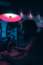 Bearded Man Drinking Beer In A Pub At Night