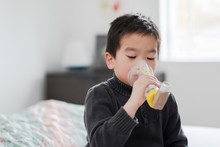 Boy Using Asthma Inhaler At Home