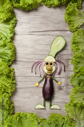 Funny cook made with vegetables on wooden board