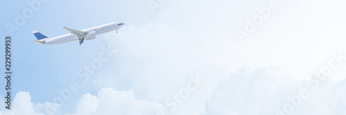 Poster Airplane Commercial airplane flying over bright blue sky and white clouds. Photo Design in banner cover size with copy space for travel concept.