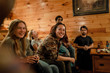 A group of friends smile and laugh on the couch in a cabin in upstate New York