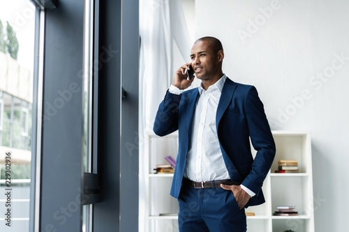 Fotografía  handsome african american businessman talking on mobile phone in modern office