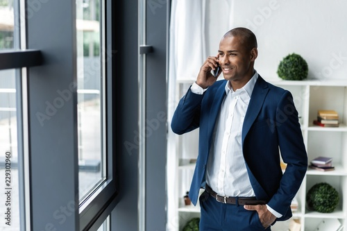 Valokuva  handsome african american businessman talking on mobile phone in modern office