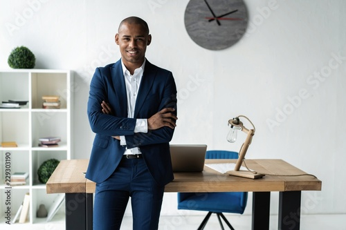 Handsome cheerful african american executive business man at the workspace office. - fototapety na wymiar