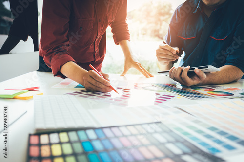 Co-worker graphic designer working with partnership choosing color on desk in modern office.