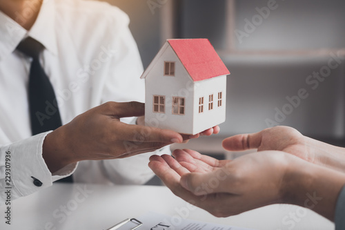 Fotografía  Real estate agent congratulations to new buyer by giving house model to client in the agency office