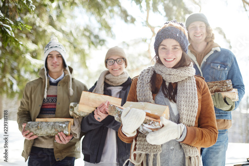 Waist up portrait of group of happy young people posing in beautiful winter forest holding logs and smiling at camera in sunlight