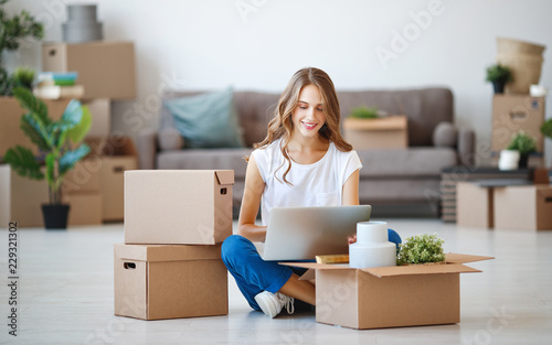 happy   girl with boxes moves to new apartment