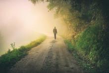 Man Walks Alone On Foggy Countryside Road.