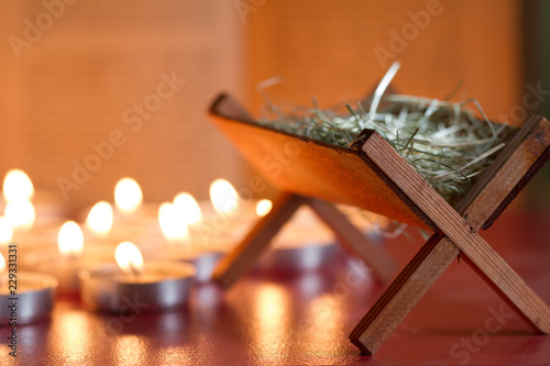 Fotografering Manger nativity scene candles and bible in night abstract background