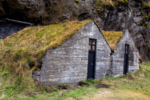 Typical Icelandic Houses Covered With Grass. Icelandic Turf Houses Covered With Grass And Cliffs In The Background. Beautiful Scandinavian Houses.