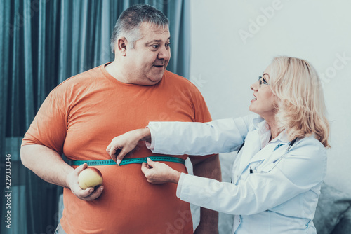 Fotografía Fat Man with Doctor in White Coat in Gray Room.