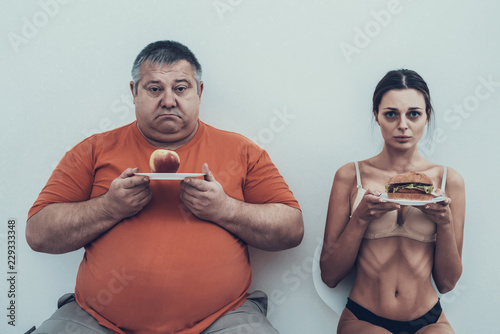 Photo Fat Man and Anorexic Girl with Plates with Food.