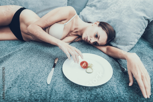 Slim Girl with Anorexia Lying on Sofa with Plate. Canvas Print