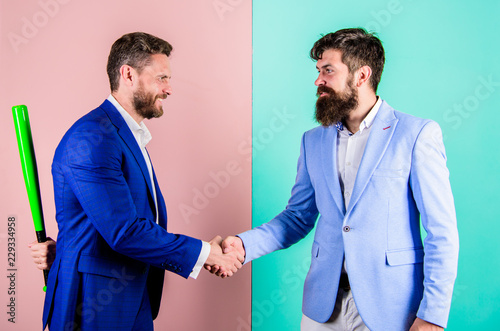 Fototapeta Business partners competitors office colleagues shaking hands. Tricky first impression. Do not trust him. Hidden danger. Businessman hides bat behind back while shaking hands. Hidden threat concept obraz