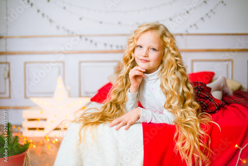 Fototapeta Little girl with blond long curly hair at Christmas morning.Merry Christmas.Little girl rejoices to the Christmas gift