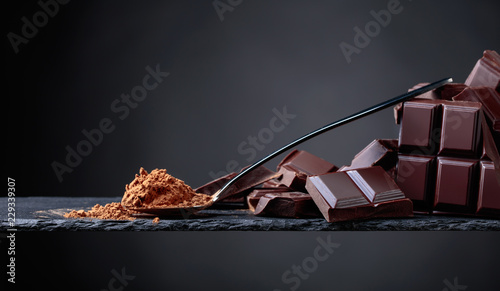 mata magnetyczna Broken chocolate pieces and cocoa powder on black background.
