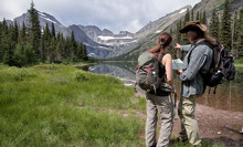 Hiker With Hiking Map In Glacier National Park, Montana, USA