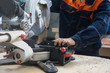 Furniture production or craft concept: worker sawing the wood surface of furniture part with saw machine