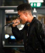 Black Rapper Performing With Microphone. Side Profile. Headphones Around Neck.
