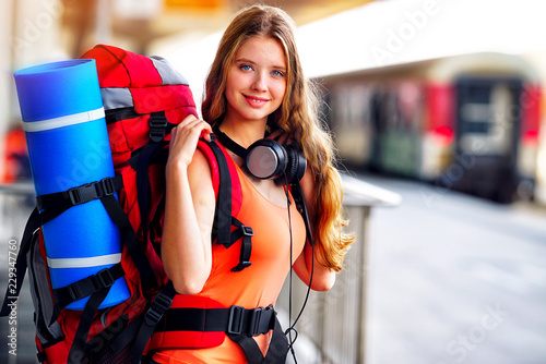 Fotografía  Traveller girl female wear headphones with backpack and tourism outfit at railway station city outdoor