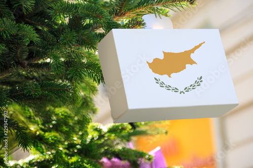 Cypriot flag printed on a Christmas gift box. Printed present box decorations on a Xmas tree branch. Christmas shopping on Cyprus , sale and deals concept.
