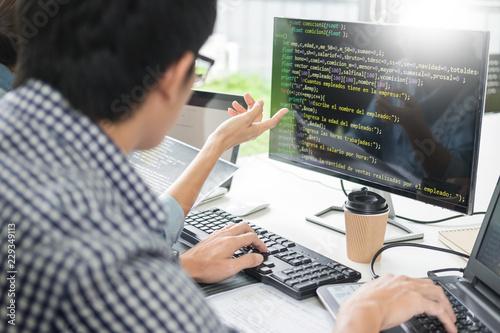 Fototapeta Asian team Outsource Developer Looking Screen Programming Code Working with Laptop Computer Software. obraz na płótnie