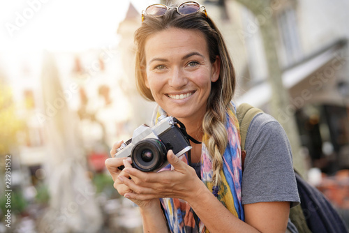 Foto  Attractive young woman taking photographs on SLR