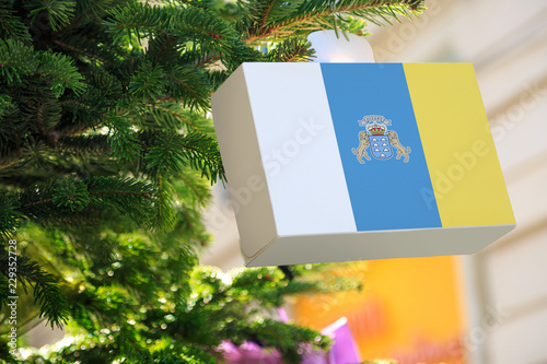 Poster Canarische Eilanden Canary Islands flag printed on a Christmas gift box. Printed present box decorations on a Xmas tree branch. Christmas shopping on Tenerife, Gran Canaria, sale and deals concept.