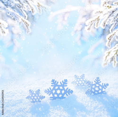 Light Christmas background. Decorative snowflakes close-up in snow on sunny day. Snowy landscape with spruce fir branches covered with snow and falling snow on nature outdoors, copy space