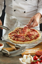 Man Dropping Sliced Meat Onto Uncooked Pizza