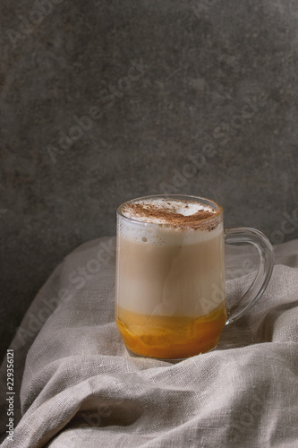 Valokuva Glass of pumpkin layered spice latte with pumpkin puree, milk foam and cinnamon standing on crumpled table cloth with grey wall at background