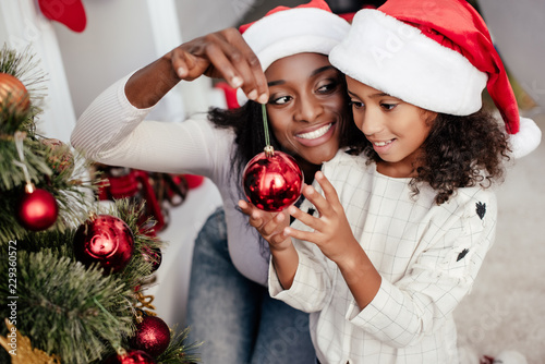 Fotografie, Obraz  smiling african american woman in santa claus hat helping daughter to decorate c