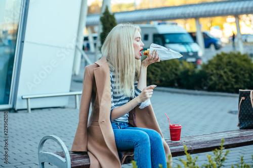 Blond hungry elegant business woman red lips having a snack with coffee and croi Canvas Print