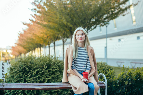 Photo  Blond thoughtful elegant business woman red lips in beige coat with coffee to go during a break sitting outdoors at the financial district with modern building ant trees perspective on background