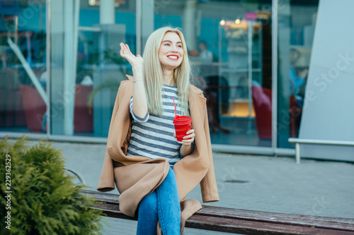 Photo Blond elegant hipster student woman red lips saying hello to someone, sitting with coffee on bench during a break outdoors at financial district with modern building on background