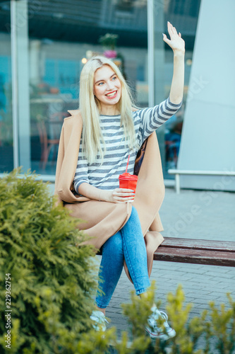 Photo Vertical full body of blond elegant student woman red lips saying hello to someone, sitting with coffee on bench during a break outdoors at financial district with modern building on background