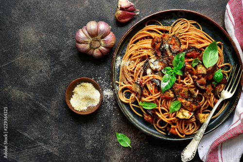 Spaghetti alla norma - traditional italian pasta with eggplants and tomato. Top view.