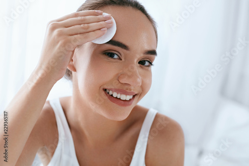 Fotografie, Obraz  Clean Face. Beautiful Woman Cleaning Skin With Cosmetic Pad