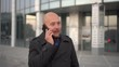 Handsome bald-headed man with beard talking on cellphone in the city. Blury steady shot