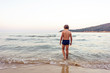 Child entering water at sunset