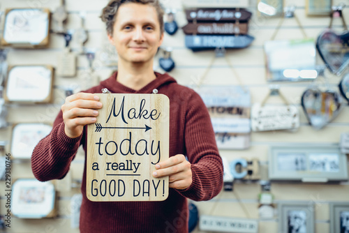 Photo sur Toile Positive Typography Portrait of Young smiling caucasian man holding motivational message typing on the wooden board. Everyday Inspirational quotes concept. Vintage styled toning. Selective focus.