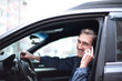 closeup.smiling man talking on mobile phone in the car.