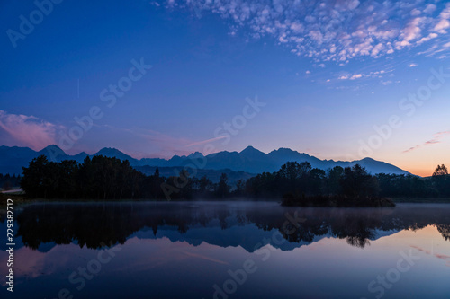 Keuken foto achterwand Meer / Vijver Blue hour shot of peaceful scene of beautiful autumn mountain landscape with lake, colorful trees and high peaks in High Tatras, Slovakia.