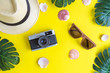 Flat lay of hat, photo camera, sunglasses, shells and tropical palm tree leaves isolated on yellow.