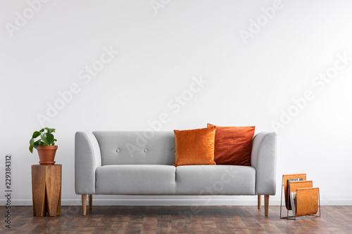 Comfortable couch with orange and red pillow in spacious living room interior, r Canvas Print