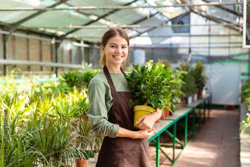 Image of caucasian woman gardener 20s wearing apron standing with plants in hand Fotobehang