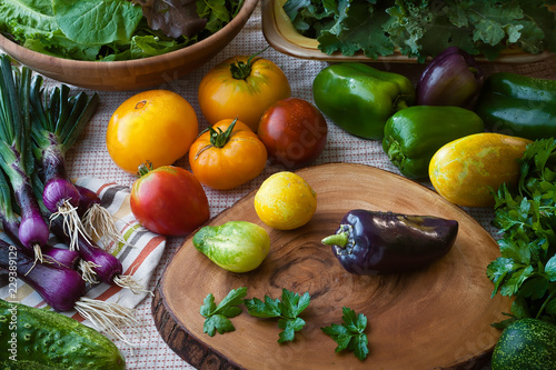 Photo Kitchen scene of just washed super foods including cucumber, purple onions, mixed greens, tomatos, kale, green pepper, and parsley with fabric and wooden cutting board