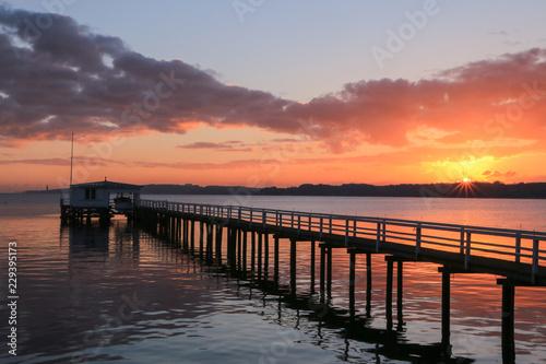 Tuinposter Baksteen malerischer Sonnenuntergang und dramatische Wolken an einer schönen Seebrücke